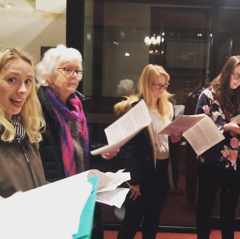 Take Note busy rehearsing in a winters evening in 2019 with musical scores in hand